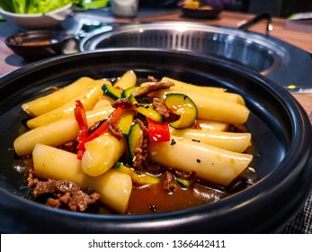 a close up of a Korean Tteokbokki rice dumplings black dish in an korean ethnic restaurant with sweet ganjang soy sauce meat and zucchini bell peppers veggies .