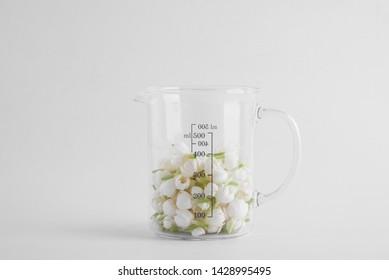 Close up of lab transparent beaker half full of fresh white jasmine flowers isolated on white background