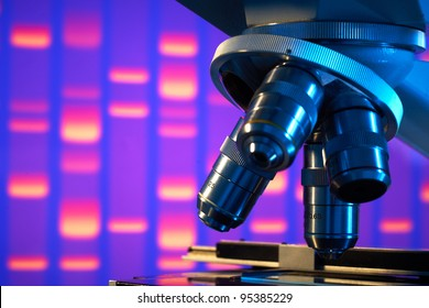 Close up of laboratory microscope with DNA gel image background