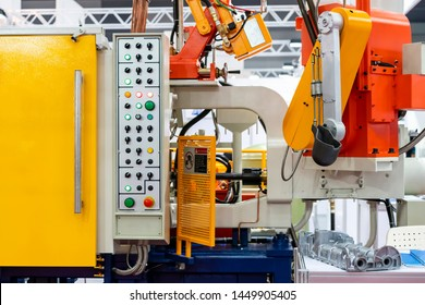 close up ladle and mechanical arm of high pressure aluminum die cast machine and other detail such as control panel etc for automobile or vehicle part manufacturing at factory or work shop