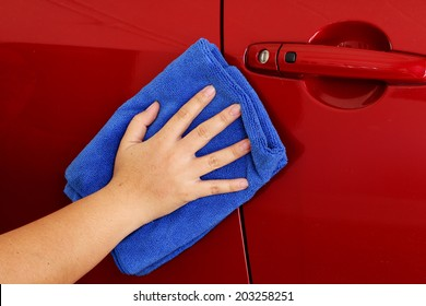 close up lady hand clean red car