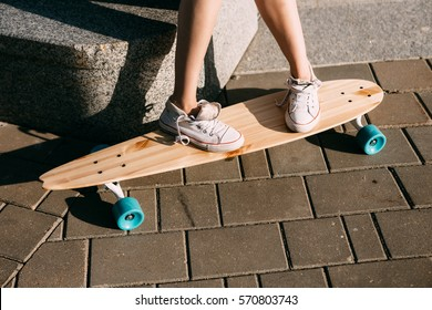 Close up of lady leg in white sneakers resting after extreme funny ride her wooden longboard skateboard. Modern urban hipster girl have fun. Good sunny summer day for skateboarding and have fun.