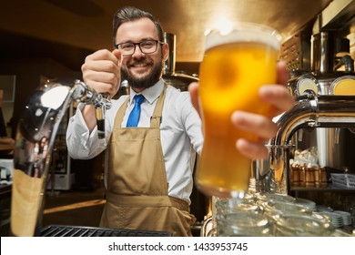 Close up of lager beer glass with foam in hand of adult, bearded, positive bartender. Handsome brewery worker in brown apron holding cold glass with dew, posing, looking at camera.
