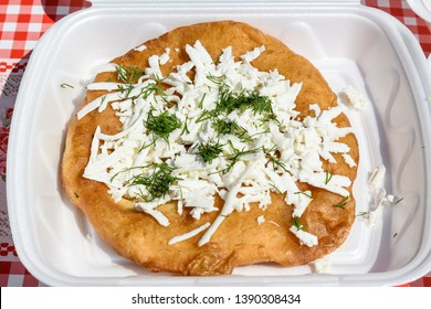 Close up of a langos, typical Hungarian food specialty, with cheese and dill on a white dish ready for take away, deep fried donut in direct sunlight at a food market