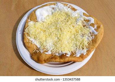 Close up of a langosi, typical Hungarian food specialty, with sour cream and cheese on a white dish on a wooden table, deep fried dough in direct sunlight at a food market
