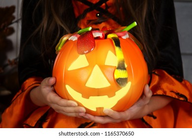 Close up of lantern jack halloween pumpkin basket for candies and sweets holded by young girl child kid in costume of halloween witch. Ready for halloween celebration concept.