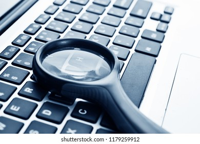 Close up of laptop with magnifying glass.