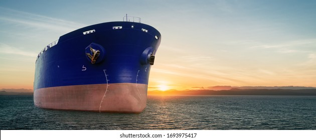 Close up of large blue merchant crago ship in the ocean underway at sunrise or sunset. Performing cargo export and import operations with sun rays, horizon line and beautiful sky.