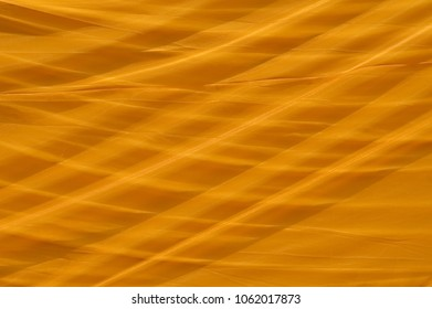 Close up of a large sheet of orange material covering a reclining buddha in Thailand.