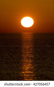 A close up of a large yellow sun rising over the ocean in the morning.