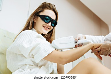 Close up Laser hair removal in the beauty salon. Woman having hands epilation.