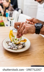 Close up of latin cook cooking banana chifles with fake squid noodles and beluga caviar