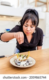 Close up of latin female cook cooking banana chifles with fake squid noodles and beluga caviar. Luxurious dinner canape, delicatessen food.