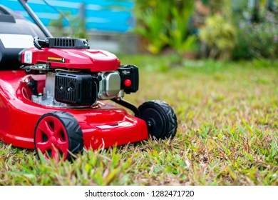 close up lawn mower in the park on the grass. over light [blur and select focus background