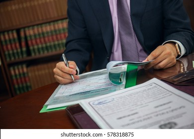 Close up of lawyer businessman sitting at table and signing document
