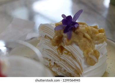 Close up of a layered crepe cake with cream and purple flower garnish, Thai style bakery