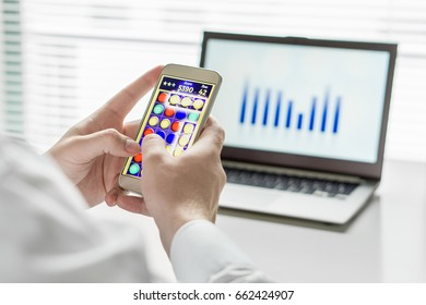 Close up of Lazy and unproductive office worker playing mobile game with smart phone during business hours. Avoiding his work. Useless and bored man doing nothing and forget his job.