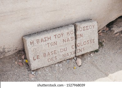 "Close up of the Le Base du Colosse des Naxiens (""The Base of the Colossus of the Naxians"") sign on the island of Delos, Greece, an archaeological site near Mykonos in the Aegean Sea."