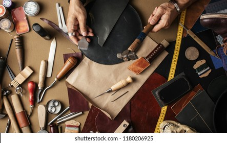 Close up of leather designer hands making custom made shoes working with genuine leather and hammer at a workshop.