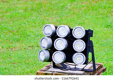 Close up of LED spotlights in the green field. Energy saving outdoor floodlights, small reflectors on green grass. A ground spotlight in green yard with green garden background.