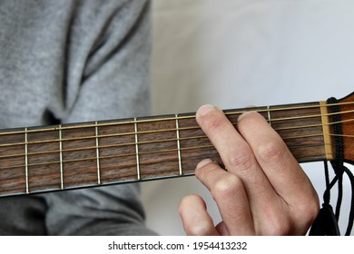 Close up of a Left Hand Playing a G Chord  on a Steel Strings Acoustic Guitar