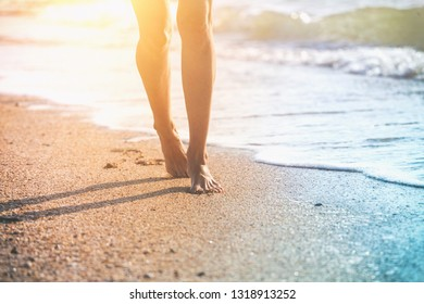 close up leg of young woman walking along wave of sea water and sand on the summer beach. Travel Concept.
