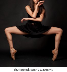 Close up legs of ballerina dancer in studio on dark background