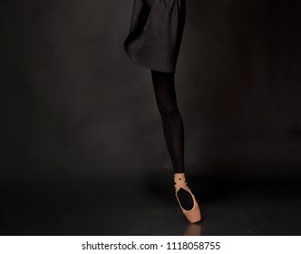 Close up legs of ballerina dancer in studio on dark background