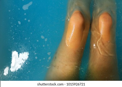 close up legs in the blue glitter water with bath bomb, foam and bubbles