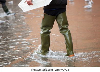 Close Up of legs with boots in the high water. This flood happens when there is high tide in Venice, Italy.