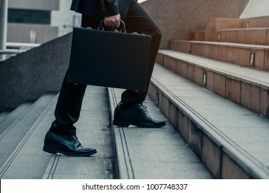Close up legs of Businessman walks with his briefcase up stair in modern city, business growth, success, grow up. Business concept.