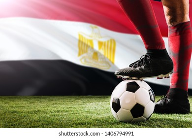 Close up legs of Egypt football team player in red socks, shoes on soccer ball at the free kick or penalty spot playing on grass.