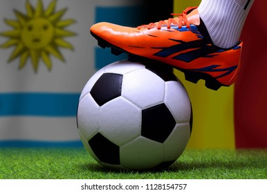 Close up legs and feet of soccer player or football player walk on green grass ready to play match on national Uruguay and national Belgium.