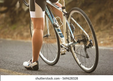 A close up to the legs of a female cyclist sitting on her road bike during sunset