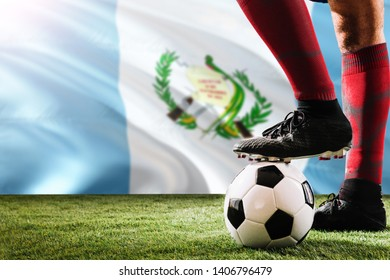 Close up legs of Guatemala football team player in red socks, shoes on soccer ball at the free kick or penalty spot playing on grass.