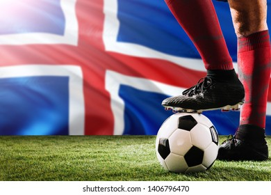 Close up legs of Iceland football team player in red socks, shoes on soccer ball at the free kick or penalty spot playing on grass.