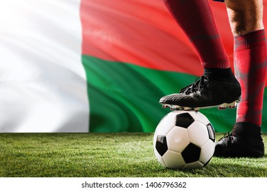 Close up legs of Madagascar football team player in red socks, shoes on soccer ball at the free kick or penalty spot playing on grass.
