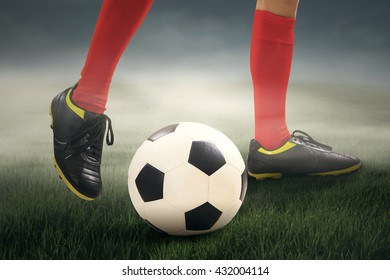 Close up of leg's man dribbles the ball at the field under cloudy sky