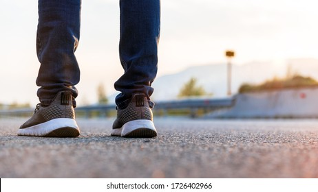 Close up legs of man standing on the highway road.