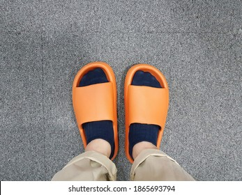 Close up legs of man wearing socks and orange rubber slipper for indoor stand on grey fabric floor background.