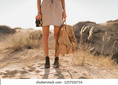 close up legs in shoes, fashion details of stylish woman in khaki dress in desert, traveling in Africa on safari, wearing boots, holding backpack, photo camera, exploring nature, summer, footwear