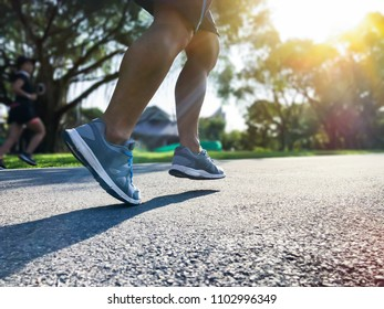 Close up legs and shoes of young runner man running with sprint on the road during sunrise. Athletic running outdoor in the public park concept.