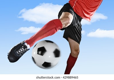 close up legs and soccer shoe of football player in action outdoors kicking ball isolated on blue sky background wearing red jersey and sock