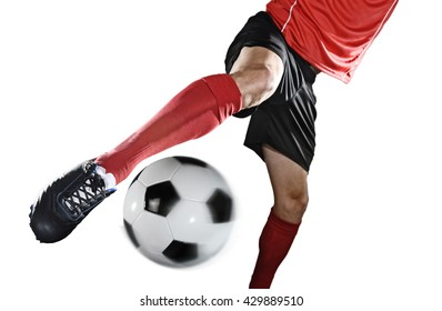 close up legs and soccer shoe of football player in action kicking ball isolated on white background wearing red jersey and sock