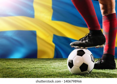 Close up legs of Sweden football team player in red socks, shoes on soccer ball at the free kick or penalty spot playing on grass.