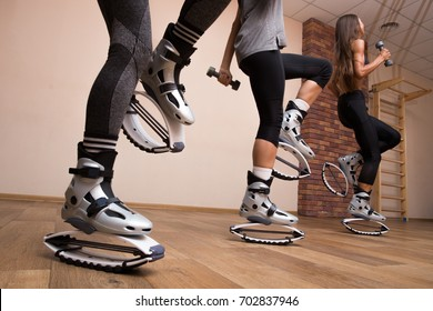 Close up of legs of three fit girls in kangoo jumping shoes. Training in the gym.