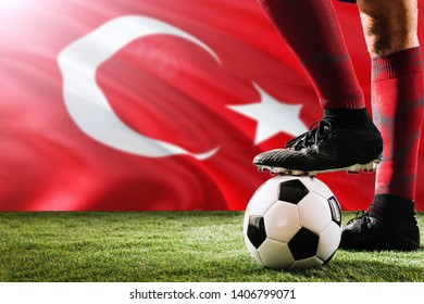 Close up legs of Turkey football team player in red socks, shoes on soccer ball at the free kick or penalty spot playing on grass.