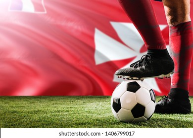 Close up legs of Wallis And Futuna football team player in red socks, shoes on soccer ball at the free kick or penalty spot playing on grass.
