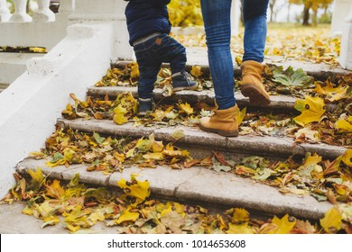Close up legs of woman walk in fall park with little child boy, climb up stairs with dry yellow autumn leaves. Mother, small kid son feet on steps. Family day 15 of may love parents, children concept