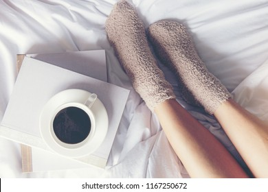 Close up legs women on white bed.  Women reading book and  drinking  coffee in morning relax mood in winter season.   Lifestyle Concept.